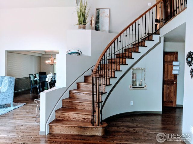 sweeping entry staircase with iron balusters