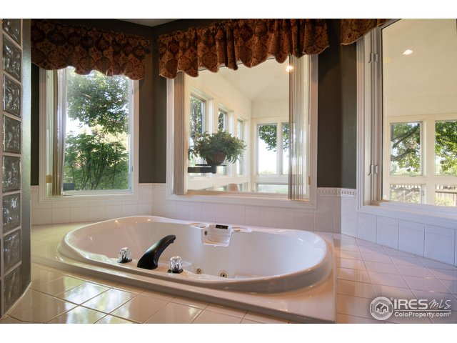Jetted tub looks out to sun/pool room