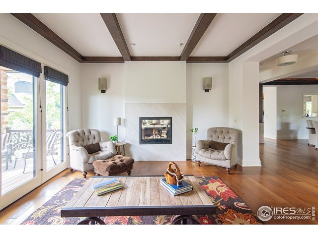 Living room features wood beams and fireplace